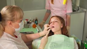 A dentist is drying a light seal on a teenage girl who came to treat her teeth stock footage