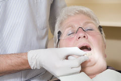 Dentist in exam room fitting dentures on woman royalty free stock photo