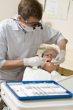 Dentist in exam room with woman Royalty Free Stock Image