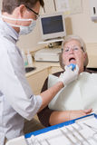 Dentist in exam room with woman Stock Photos