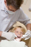 Dentist in exam room with young boy in chair royalty free stock photo