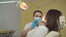 The dentist examines a female patient in the dental office. stock footage