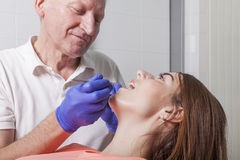 Dentist examines gums and teeth of his female patient Royalty Free Stock Image