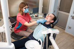 A dentist examines his patient's teeth. Action in the dental clinic Royalty Free Stock Photography