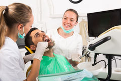 Dentist examines patient at clinic. Female dentist with assistant diagnostics the oral cavity of patient at clinic stock images