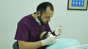 Dentist examines a  woman patient  specialist diagnosing dental care. Doctor stock video footage