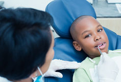 Dentist examining boys teeth in the dentists chair Stock Images