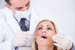Dentist examining female patient in clinic Royalty Free Stock Images