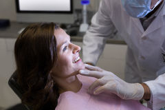 Dentist examining a female patient Royalty Free Stock Photos
