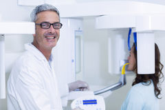 Dentist examining a female patient with dental tool Royalty Free Stock Photos