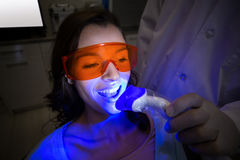Dentist examining a female patient with dental tool Stock Photos