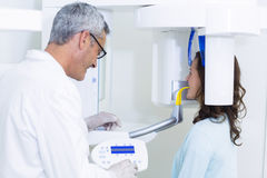 Dentist examining a female patient with dental tool Royalty Free Stock Image