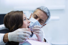 Dentist examining a female patient with tools Stock Photography