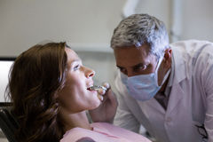 Dentist examining a female patient with tools Royalty Free Stock Photography