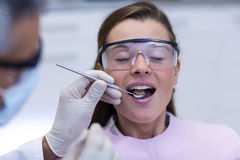 Dentist examining a female patient with tools Royalty Free Stock Images