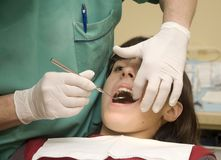 Dentist examining a girl's teeth Royalty Free Stock Photos