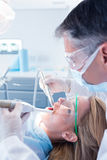 Dentist examining his patient with a suction hose Royalty Free Stock Photo