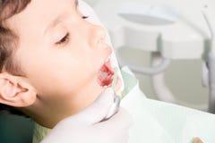 Dentist examining kid's teeth royalty free stock photos