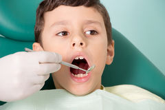 Dentist examining kid's teeth Royalty Free Stock Image