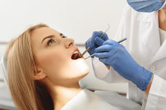 Dentist examining mouth of client Royalty Free Stock Photos