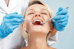 Dentist examining a patient`s teeth in the dentis stock photo