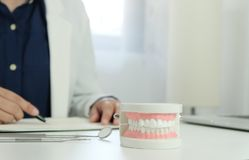 Dentist examining a patient teeth medical treatment at the dental office. stock photography