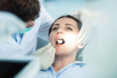 Dentist examining Patient teeth with a Mouth Mirror. Royalty Free Stock Photos