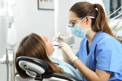 Dentist examining a patient teeth. Dentist wearing eyeglasses gloves and mask examining a patient teeth with a dental probe and a mirror in a clinic box with Stock Photo