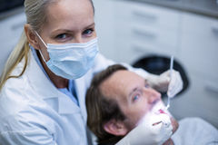 Dentist examining a patient with tools Stock Photo