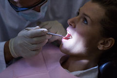 Dentist examining a patient with tools Stock Photos