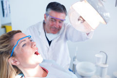 Dentist examining a patients teeth in chair under bright light Stock Photos