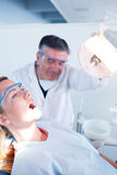 Dentist examining a patients teeth in chair under bright light Stock Images