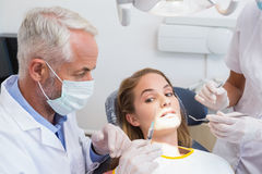 Dentist examining a patients teeth in the dentists chair with assistant Royalty Free Stock Photo