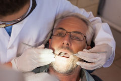 Dentist examining a patients teeth in the dentists chair Royalty Free Stock Photo