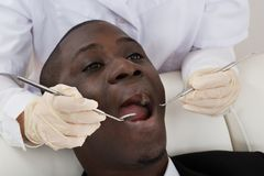Dentist Examining Teeth Of Patient Stock Photo