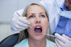 Dentist examining a woman with tools Royalty Free Stock Images