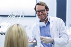 Dentist examining a woman with tools Royalty Free Stock Photos