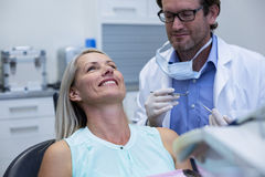 Dentist examining a woman with tools Royalty Free Stock Photos