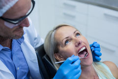 Dentist examining a woman with tools Royalty Free Stock Photo