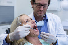 Dentist examining a woman with tools Stock Image