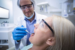 Dentist examining a woman with tools Stock Images