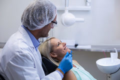 Dentist examining a woman with tools Royalty Free Stock Image