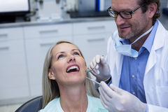 Dentist examining a woman with tools Stock Photos