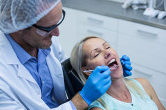 Dentist examining a woman with tools Stock Photography