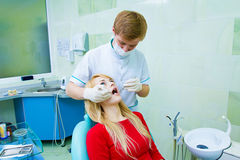 Dentist examining young adult patient, doing cleaning of teeth stock image