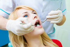 Dentist examining young adult patient, doing cleaning of teeth Royalty Free Stock Photo