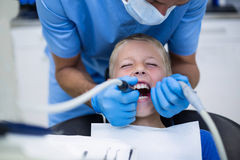 Dentist examining a young patient with tools Royalty Free Stock Images