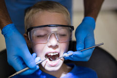 Dentist examining a young patient with tools Royalty Free Stock Photo