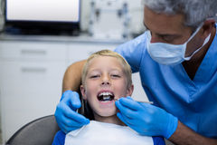 Dentist examining a young patient with tools Royalty Free Stock Photography