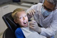 Dentist examining a young patient with tools Stock Photos